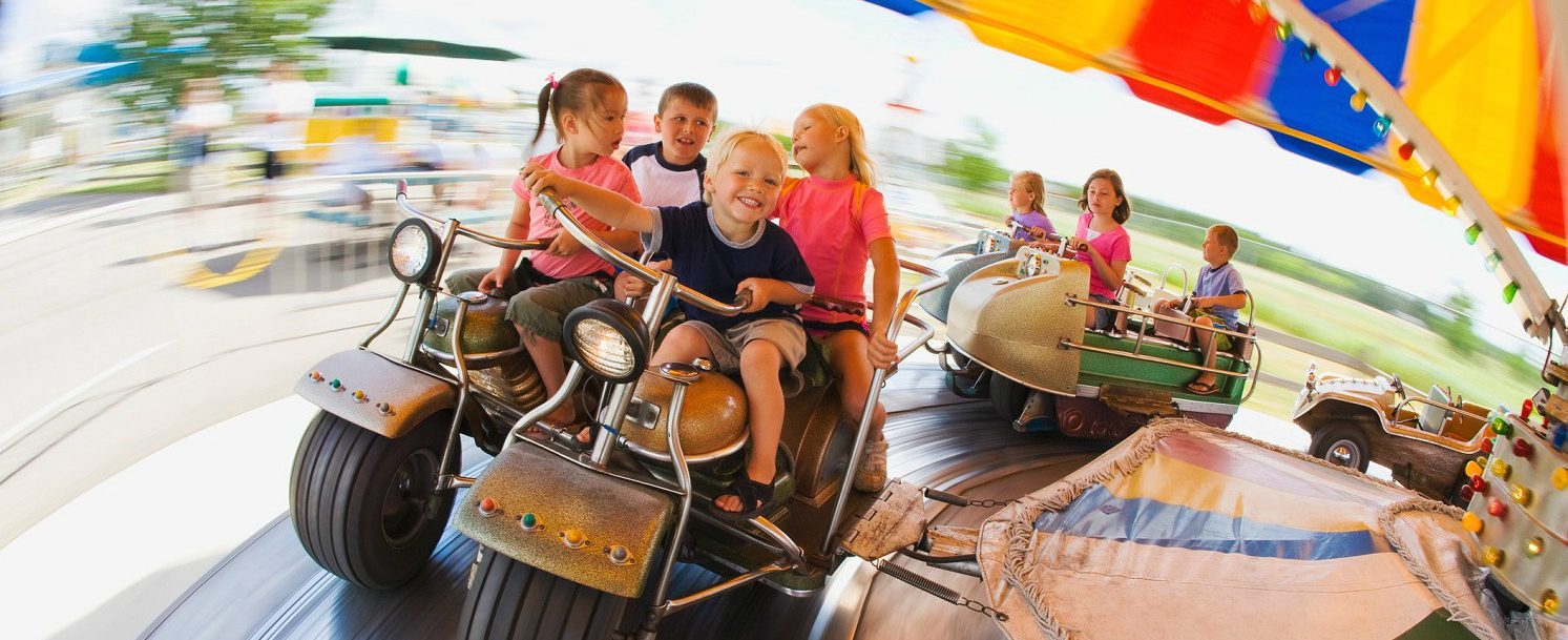 Kids on a ride at an amusement park.