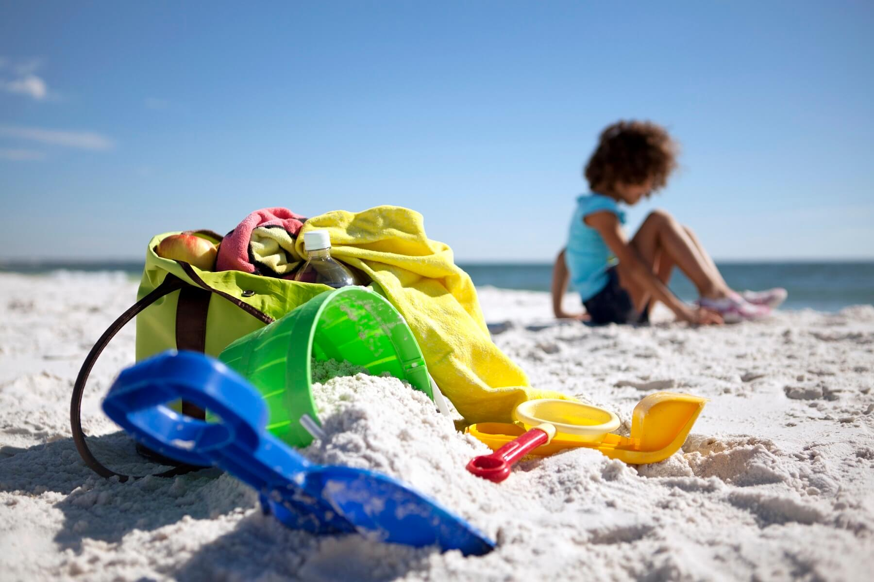 child on beach with toys