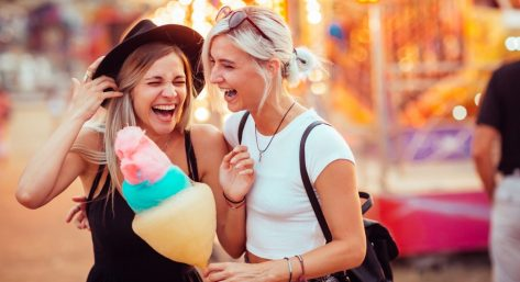 Two girls having cotton candy at an amusement park.