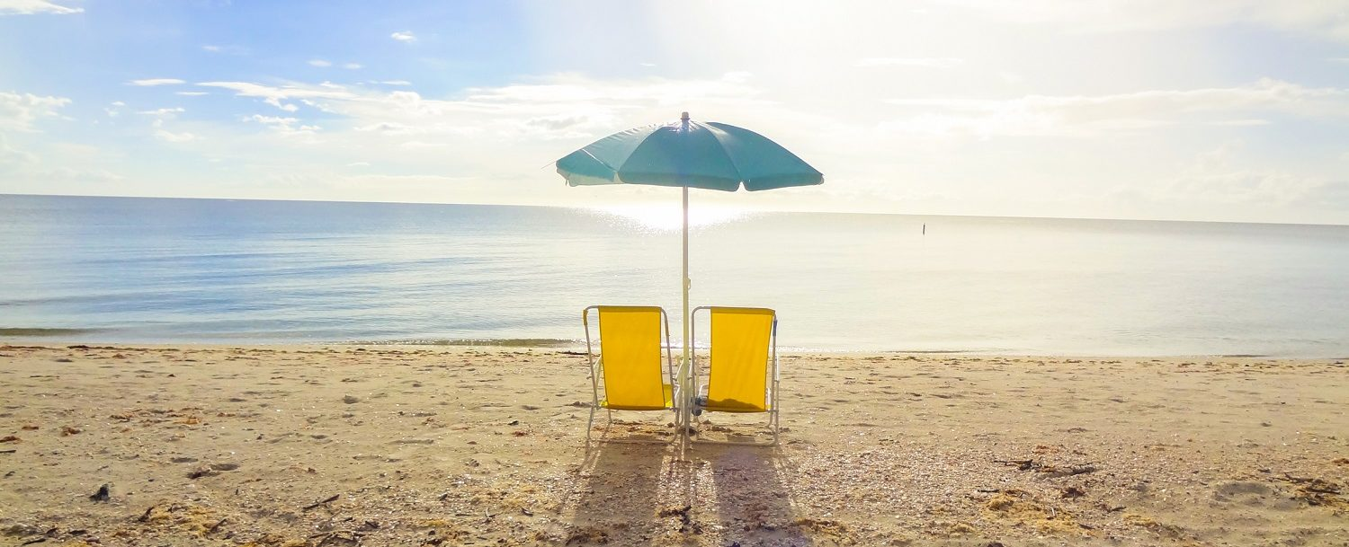 Two beach chairs on the sand.